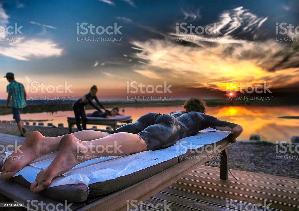 Young Woman Relaxing on Bed With Sunset Over Water stock photo