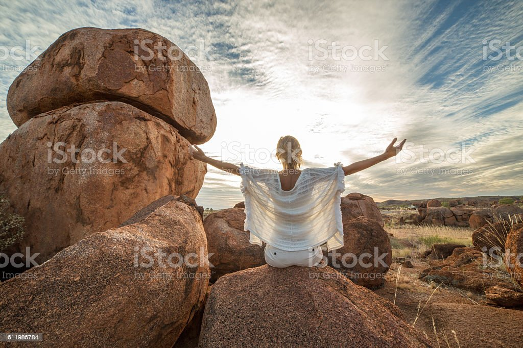 Young woman relaxing on boulder at sunset stock photo