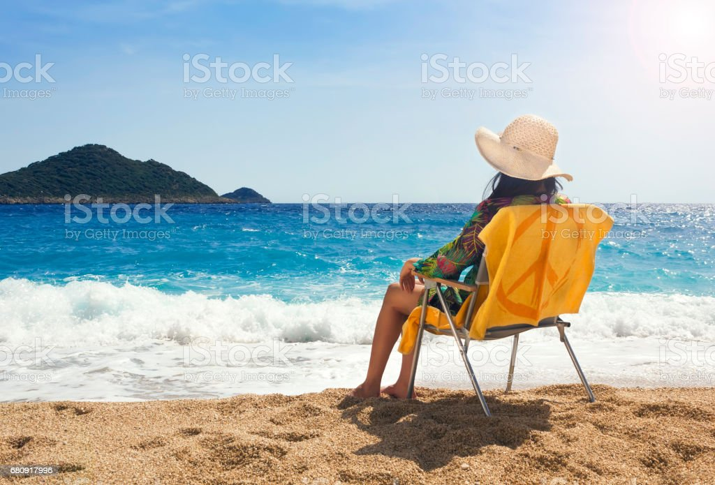 Young woman relaxing on chair on the beach royalty-free stock photo
