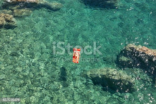 Aerial view of a young woman floating on pool mattress in the ocean.