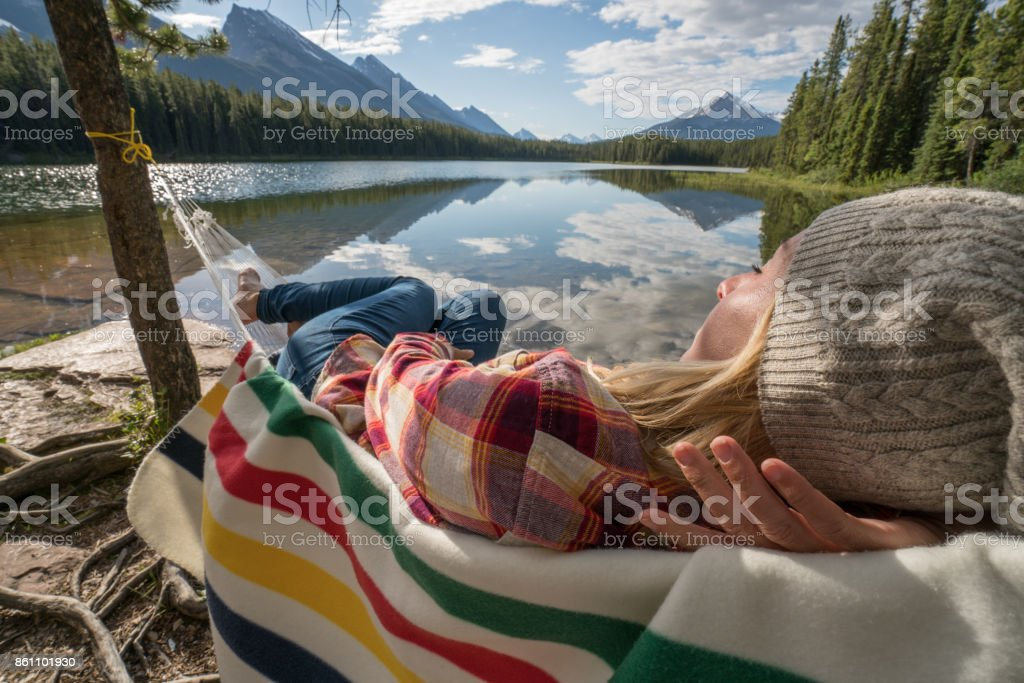 Young woman relaxing on hammock by the lake stock photo