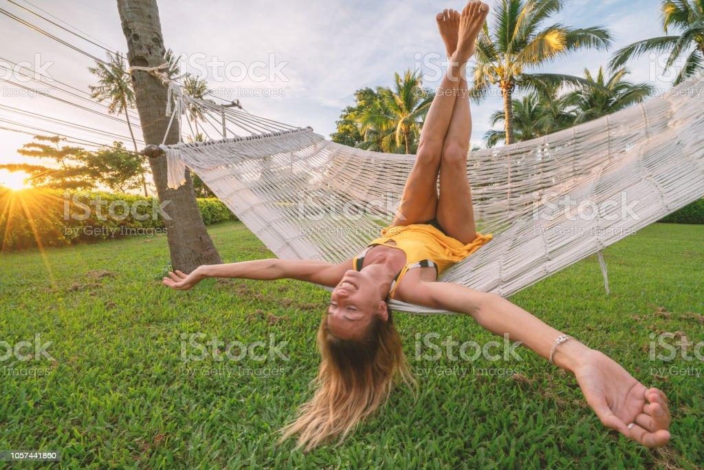 Entspannen Sie sich auf der Hängematte im tropischen Klima arme junge Frau ausgestreckten Beinen genießen ruhige Umgebung mit Palmen und grünen Rasen Garten. Menschen reisen Konzept im Urlaub entspannen – Foto