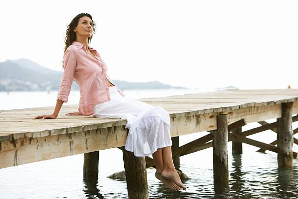 junge frau entspannend auf anlegesteg - damen rock pink stock-fotos und bilder