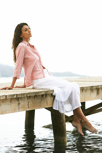 Young woman relaxing on jetty stock photo