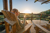 Young woman relaxing on the terrace of her wooden lodge at sunset with a glass of wine. Idyllic setting by the sea, shot in the Southern Tip of Africa, Cape Agulhas.