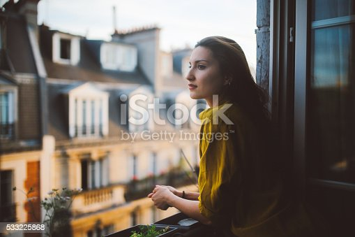 Vintage toned image of a young woman relaxing, enjoying the view, on the small balcony - window of her beautiful apartment on Montmartre, Paris. Taken in the magic hour just as the sun sets down, the rooftops of the Montmartre homes can be seen in the background, lit by the evening or early morning sun.