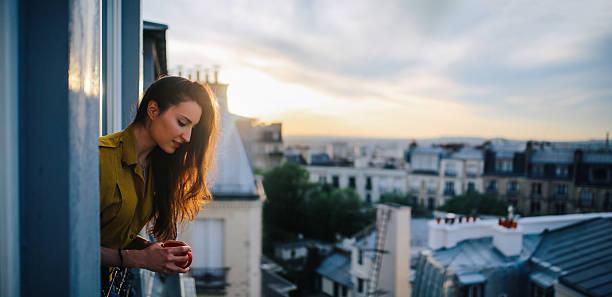 young woman relaxing on the balcony of her parisian apartment - montmatre utsikt bildbanksfoton och bilder