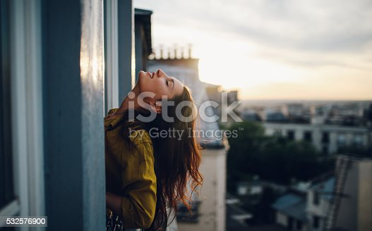 Vintage toned image of a young woman relaxing, on the small balcony - window of her beautiful apartment on Montmartre, Paris. Taken in the magic hour just as the sun sets down over Parisian city scape in the background and the sunrays paint her hair bright.