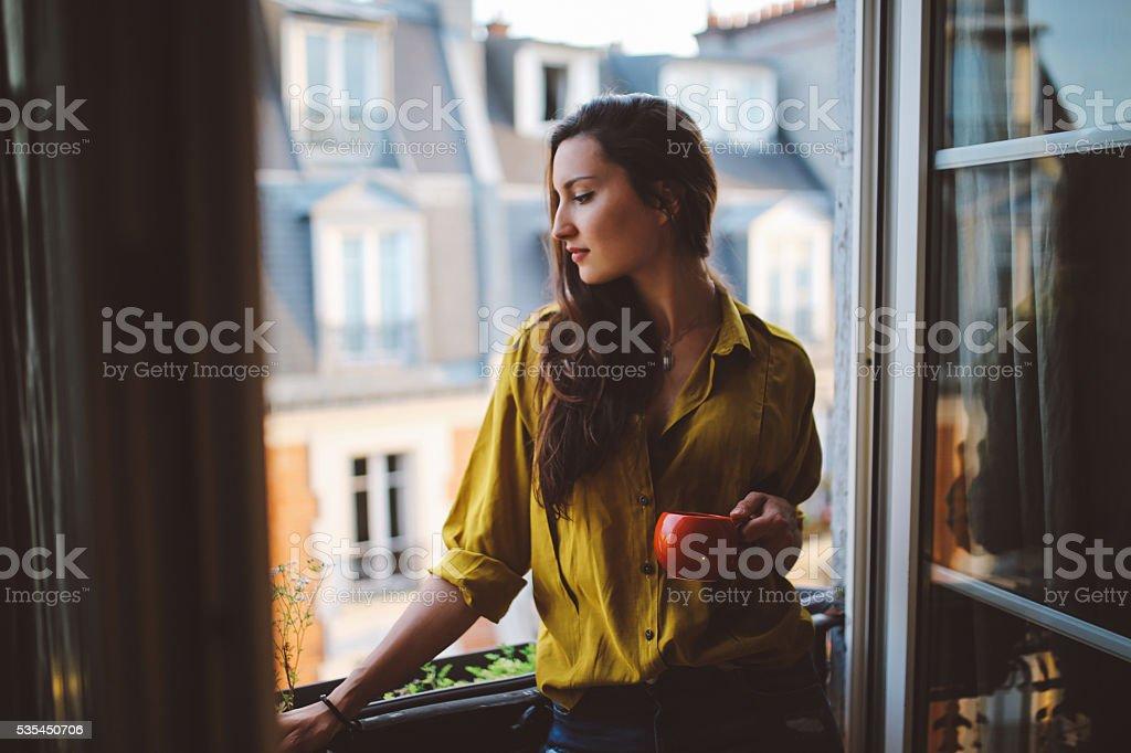 Mujer joven relajante en el balcón de su apartamento parisino - foto de stock