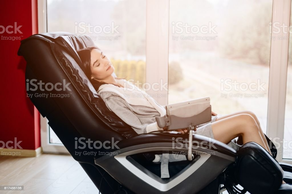 Young woman relaxing on the massaging chair stock photo