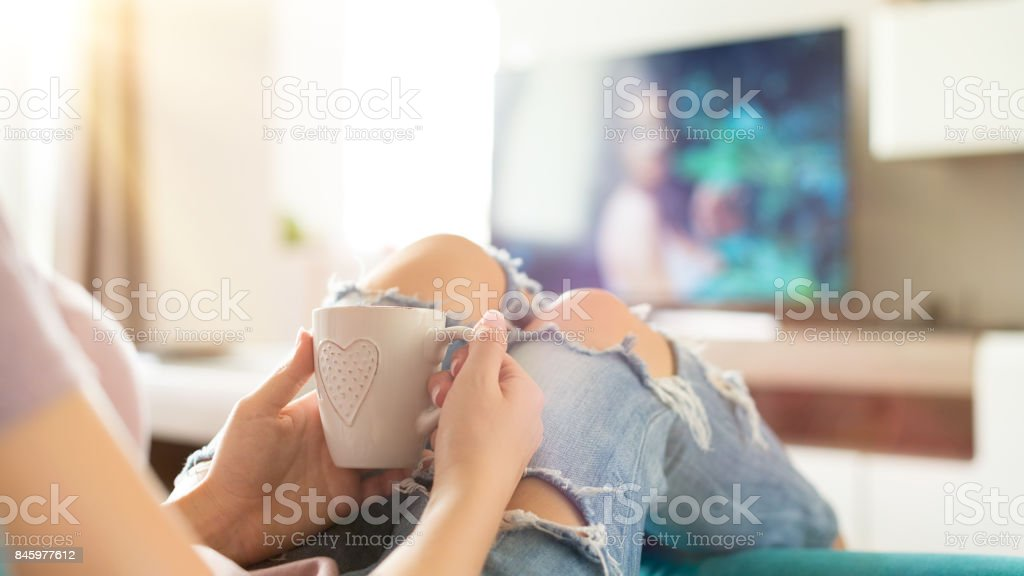 Young woman relaxing on the sofa at home, watching tv stock photo