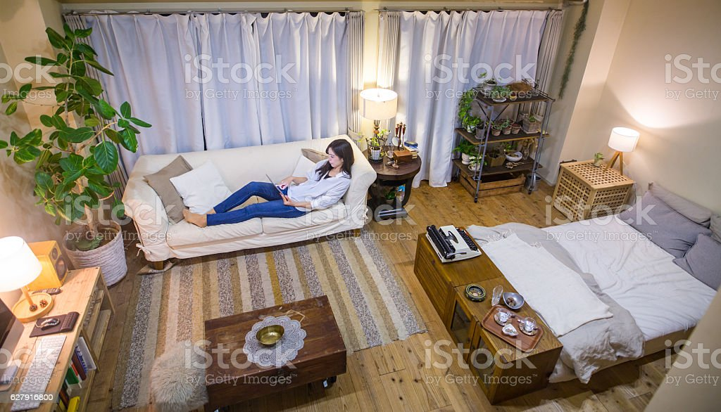 Young woman relaxing on the sofa using a digital tablet stock photo