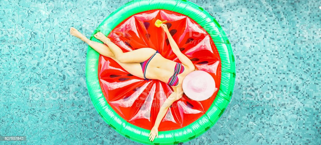 Junge Frau entspannt auf Wassermelone Lilo im Hotel Resort Pool - Draufsicht des Reiches Mädchen schwimmende mit Obst Matratze trinken cocktail - Sommer Urlaub Konzept - Fokus auf ihrem Körper - Soft gesättigt filter – Foto