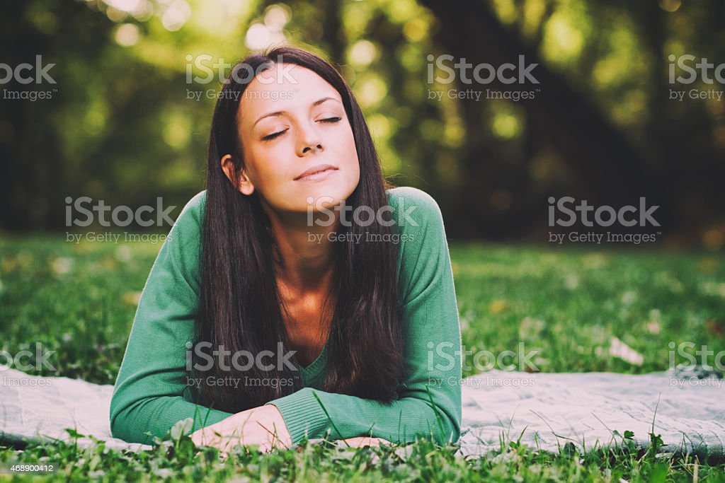 Young woman relaxing outdoors laying in the grass stock photo