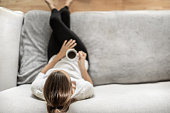 istock Young woman relaxing sitting on sofa enjoying a cup of coffee. 1277215741
