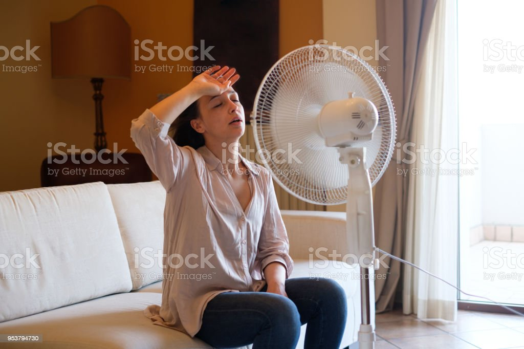 Young woman relaxing under the air fan at home stock photo