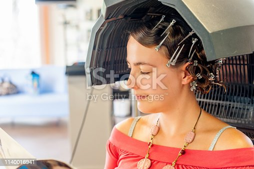 Young woman relaxing while waiting under the dryer in the Hair salon