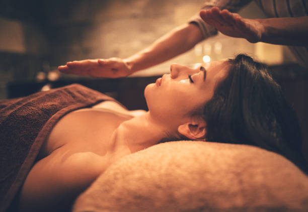 young woman relaxing with body and face massage at spa - holistic medicine stock photos and pictures