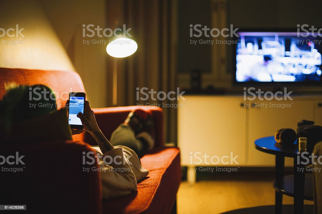 Young woman relaxing with smartphone on sofa stock photo