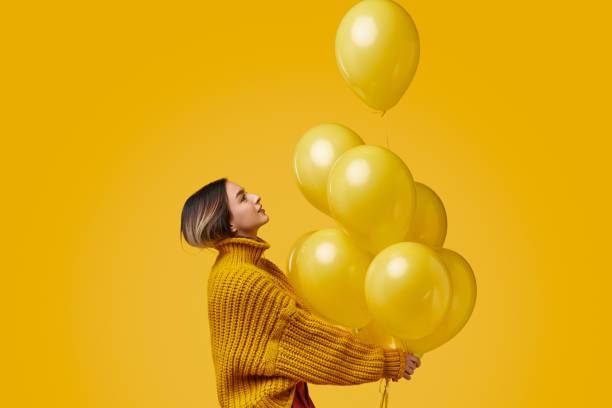 young woman releasing balloons - mulher balões imagens e fotografias de stock