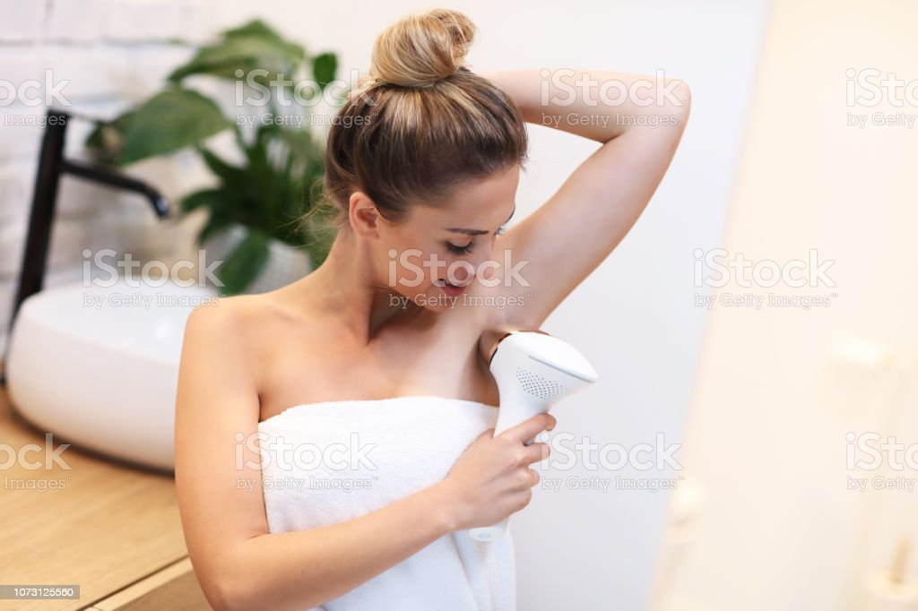 Young woman removing hair from armpits in bathroom stock photo