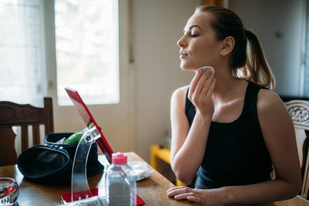 若い女性の化粧を落として鏡を ストックフォト