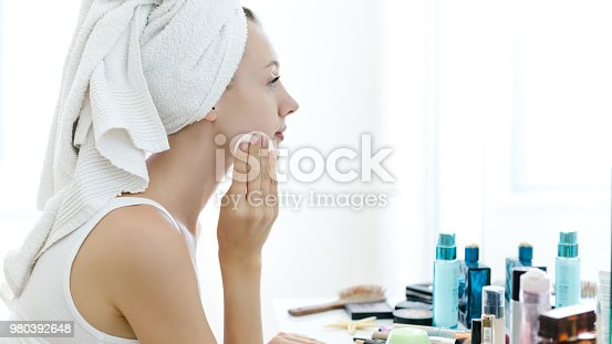 istock Young woman removing makeup from her face 980392648