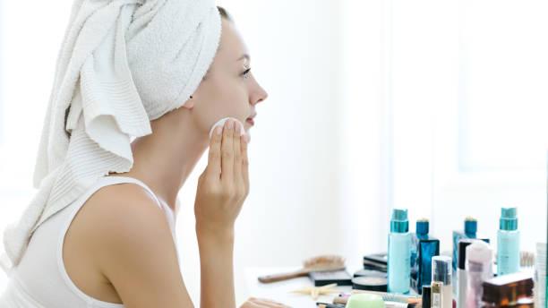 若い女性が彼女の顔から化粧を削除します。 ストックフォト