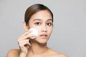 若い女性が化粧を削除します。肌ケアのコンセプトです。