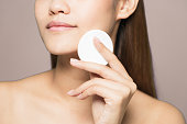 Young woman removing makeup. Skin care concept.