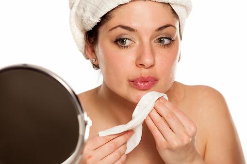 一個年輕的女人脫下化妝與濕巾 照片檔及更多 乾淨 照片