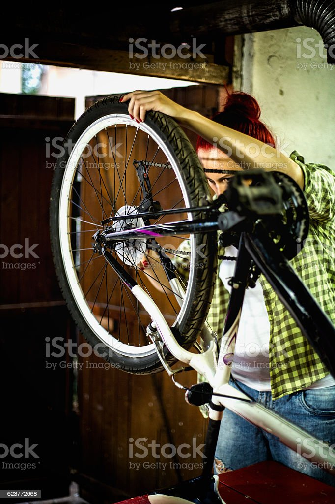 Young woman repairing bicycle wheel stock photo