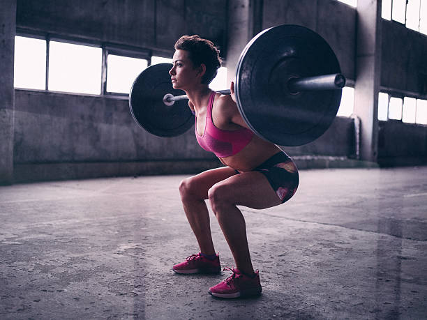 Young woman resting a heavy barbell on her shoulders stock photo