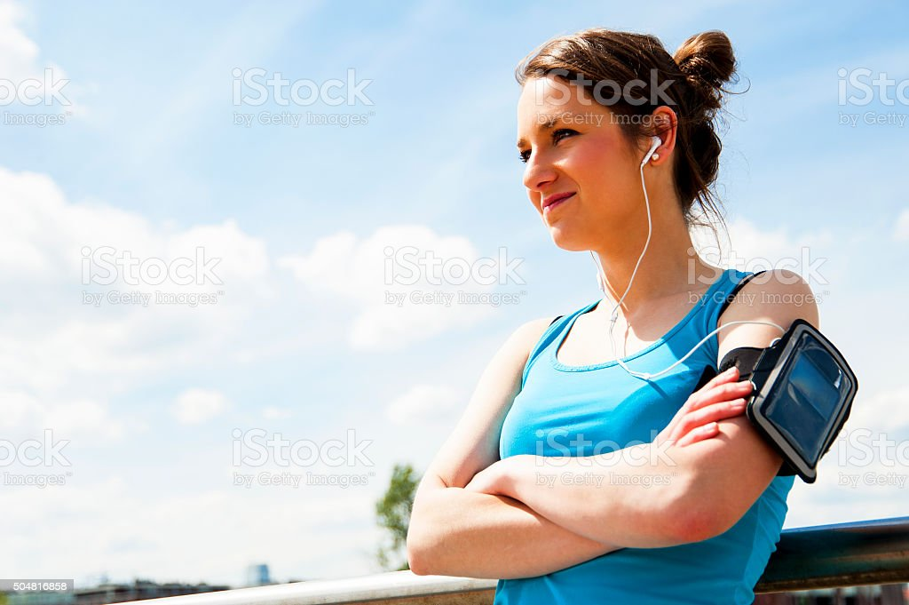 Young woman resting after run. In blue sportswear. stock photo