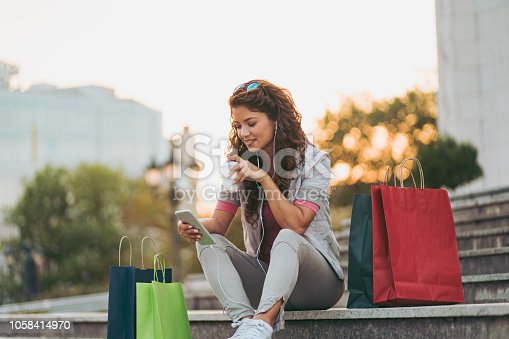 Young woman resting after shopping and listening to music