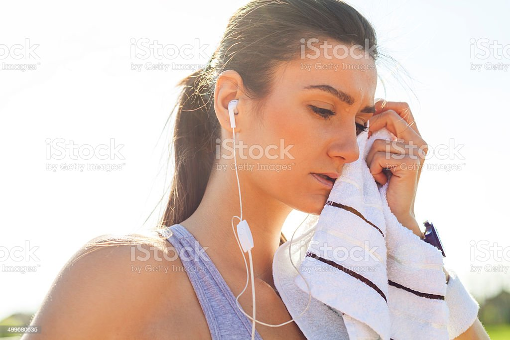 Young woman resting and wiping with towel after running. stock photo