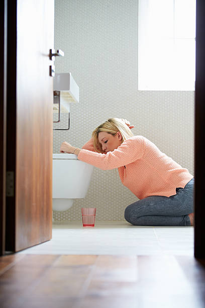 A young woman resting by a toilet in the bathroom stock photo