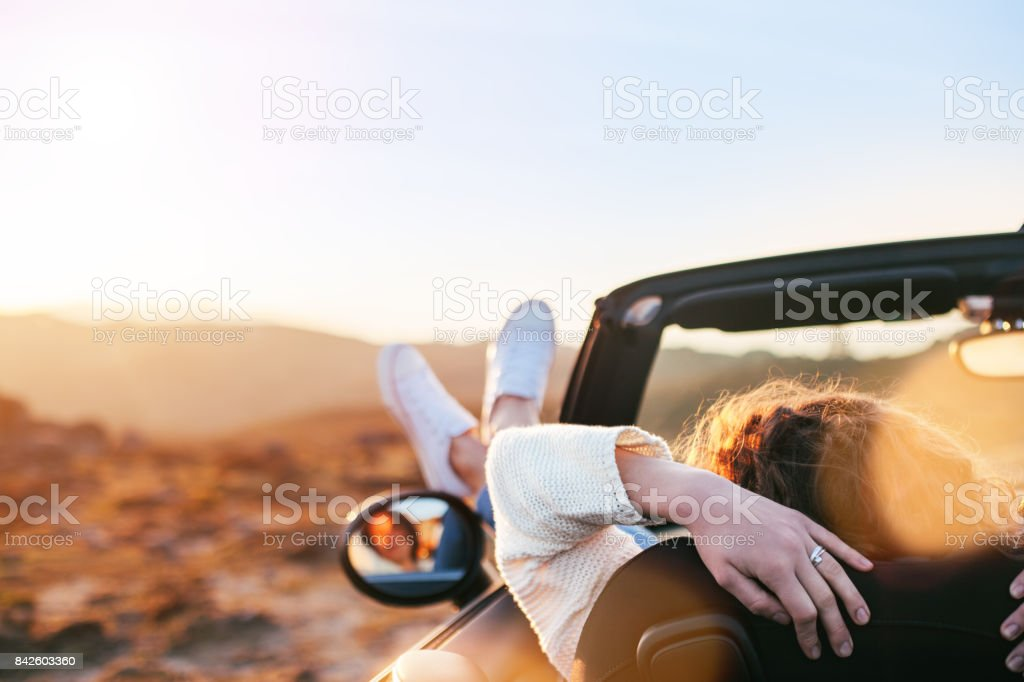 Young woman resting in convertible - fotografia de stock