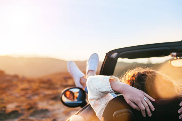 Young woman resting in convertible stock photo