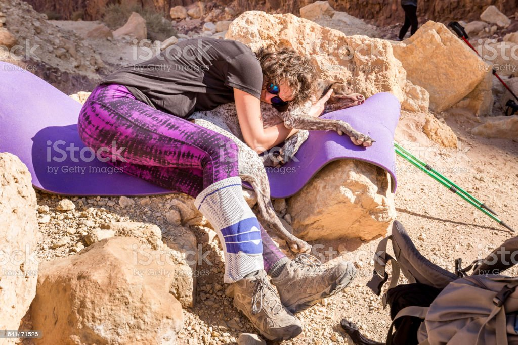 Young woman resting leaning dog travel hiking desert stone. stock photo
