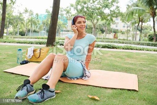 Smiling young woman sitting on yoga mat on campus and listening to music in headphones