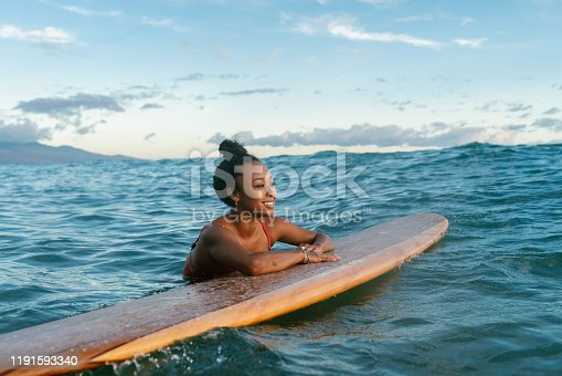Young woman resting on her surfboard waiting for a wave. Hawaii 2019