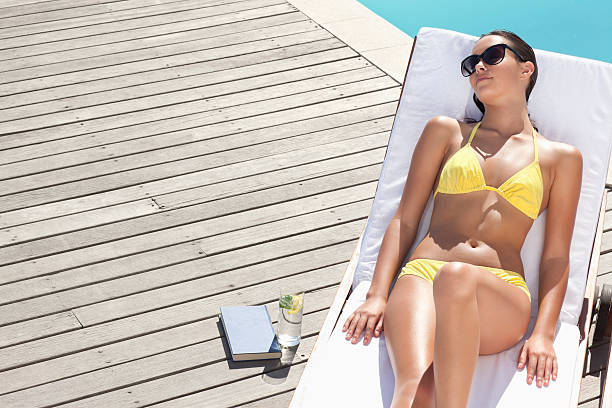 Young woman resting on lounge chair at poolside stock photo
