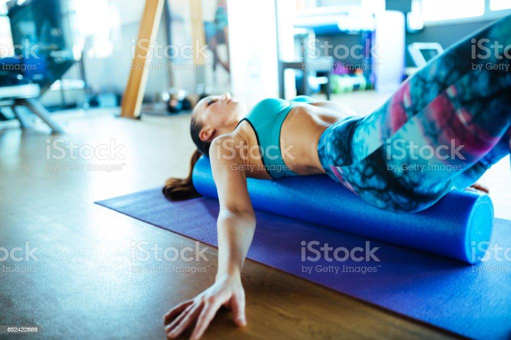 Mujer joven apoyada en el rodillo de la espuma de pilates - foto de stock