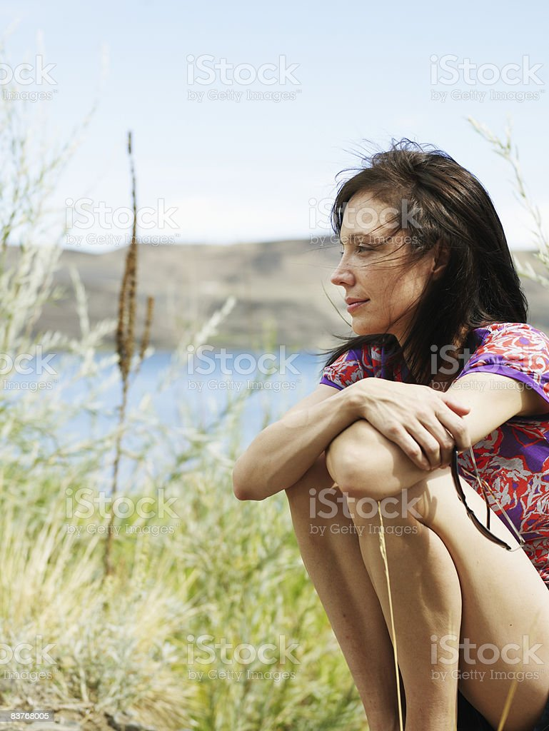Young woman resting outdoors, hair blowing in wind royalty free stockfoto