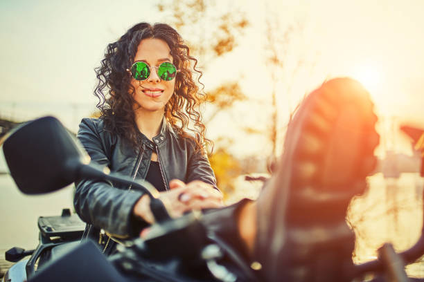 Young woman resting sitting on a motorcycle . Travel and tourism concept stock photo