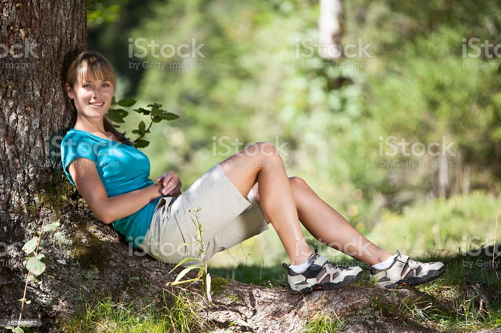 Young woman resting under tree,smiling,portrait stock photo