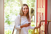 Young Woman Returning Home For Work With Shopping, Smiling