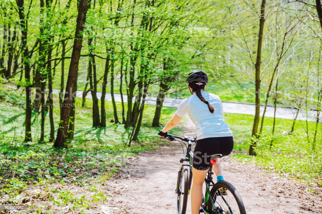 young woman ride bicycle in forest by trail - Royalty-free 20-29 Years Stock Photo