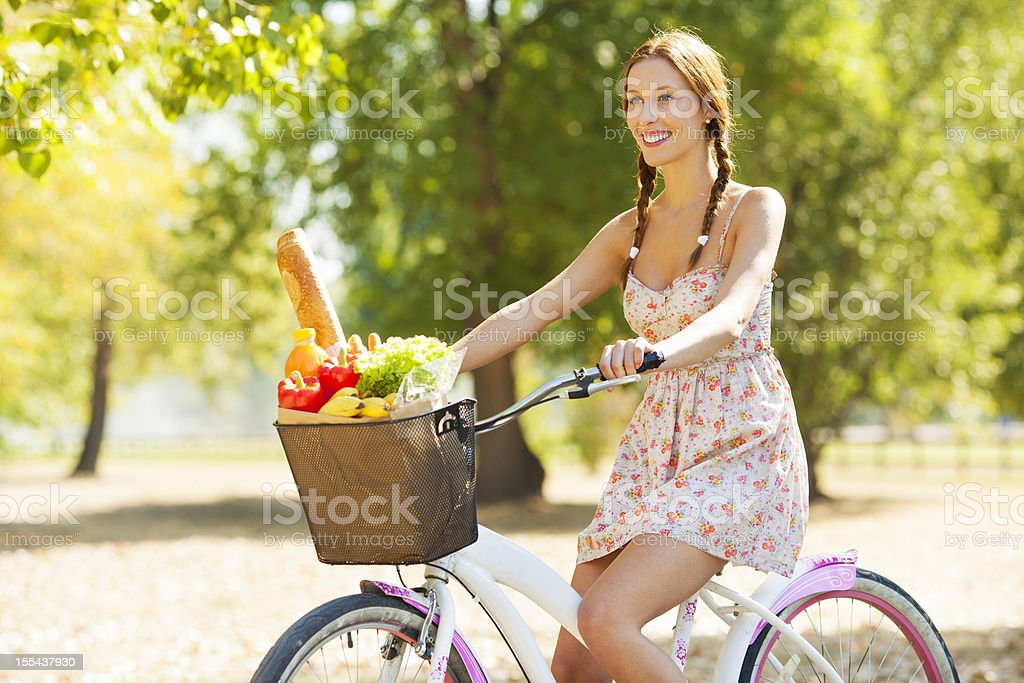 Young Woman Ride Bicycle with shopping bag full of groceries. royalty-free stock photo